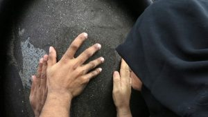 women touching black stone