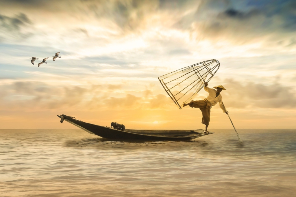 Fisherman standing on a small boat