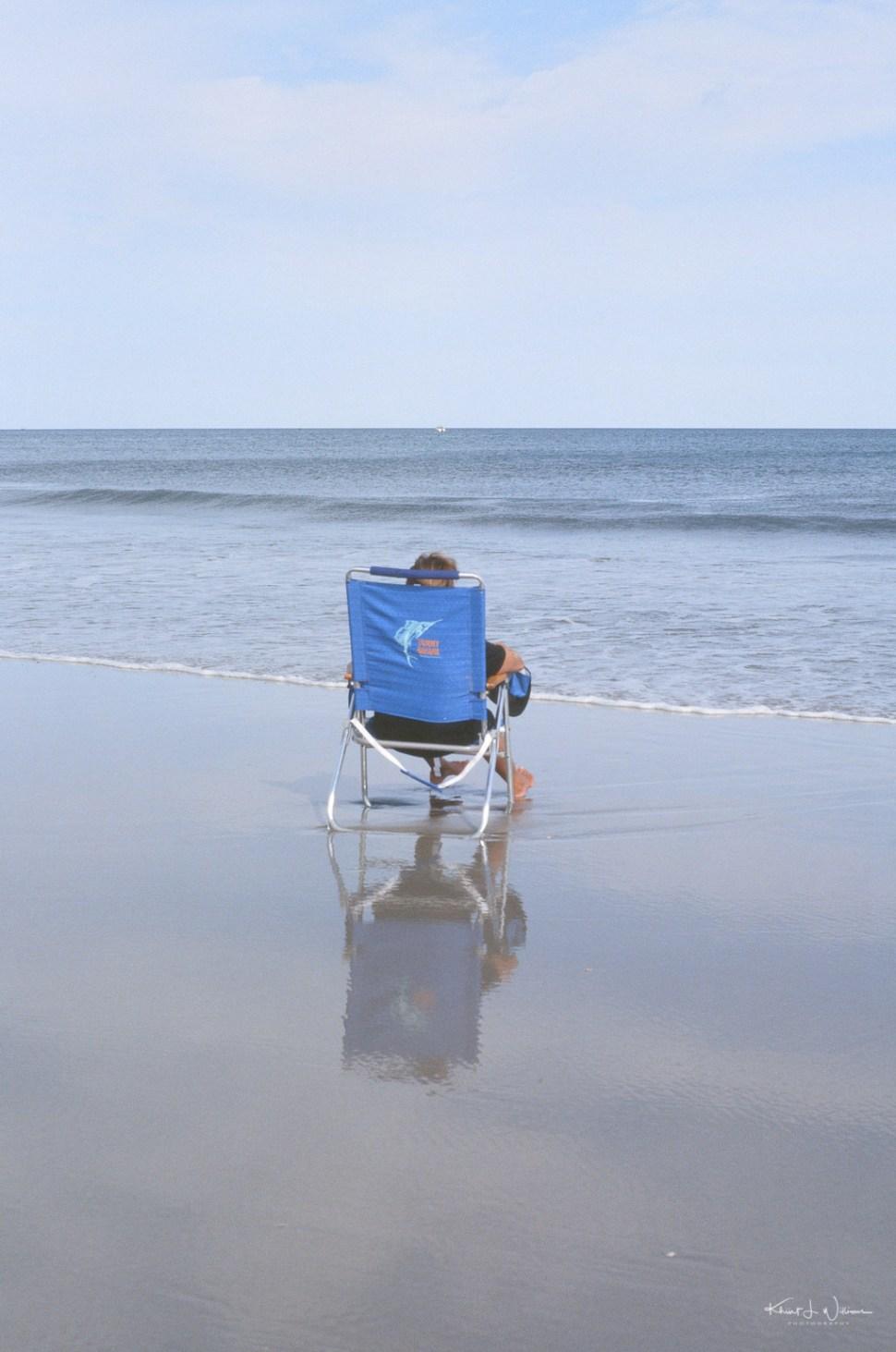 Woman sitting on beach chair on Avalon Beach