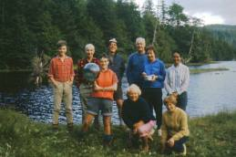 Group photo, probably end of trip at the lagoon near the pickup location for the float plane. Ruth Master's holding glass ball. Phyllis Hill red hair first row. Bill Hill, taller blue shirt.