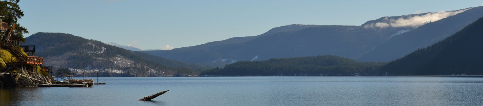 sproat lake with cabins in view and mountains in background