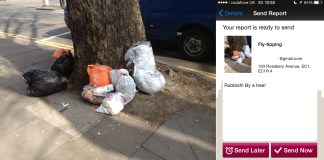 Rubbish by a tree next to my report of the rubbish,