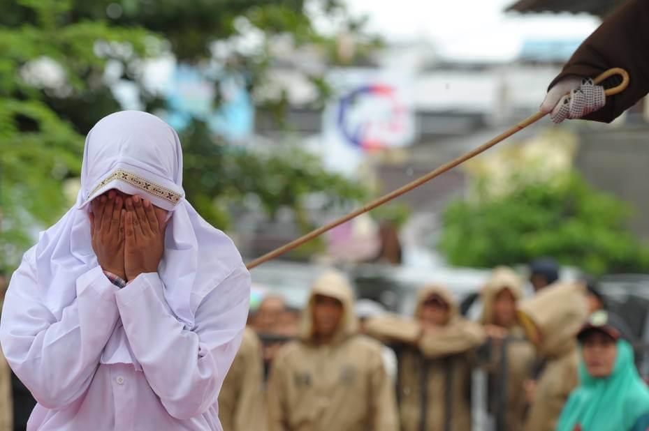 Una mujer azotada a principios de este año por prostitución llora en público durante la ejecución de la sentencia. Imagen: AsiaNews