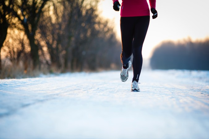 Winter running - Young woman running outdoors on a cold winter d
