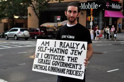 """Protesters stand silently during the demonstration holding their placards and signs. -- The """"Jews Say No"""" movement held a protest in Upper Manhattan expressing their opposition to the recent air attacks on the Gaza strip. Protesters stood silently, holding posters and placards which voiced their concerns. New York, USA. 22nd August 2011"""