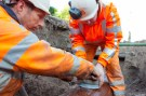 twee grondwerkers maken aftakking op rioolbuis