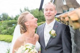 Bruid lacht naar Bruidegom die naar de camera kijkt