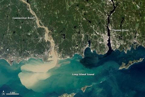 Аэроснимок с Новой Англии, показывающий впадение половодной реки в океан. Вода коричневая из-за наличия осадка
