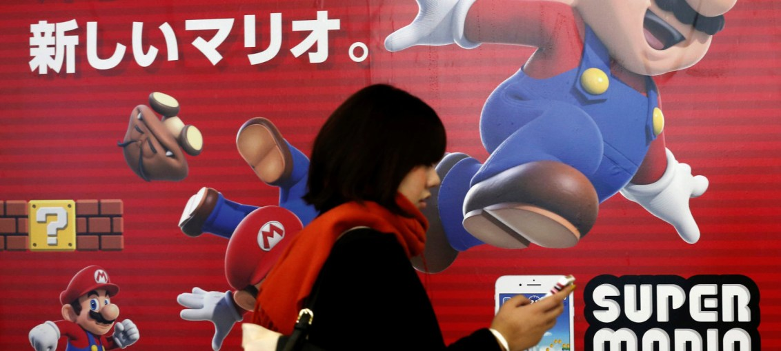 "A woman using a smartphone walks past Nintendo's ""Super Mario Run"" game advertisement board at a subway station in Tokyo, Japan"