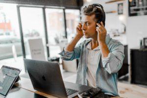 Ein Man sitzt in einem Kaffee und nimmt an einem Web-Meeting teil. Das ist Kernelement eines virtuellen Teams. Bild: Unsplash/Austin Distel