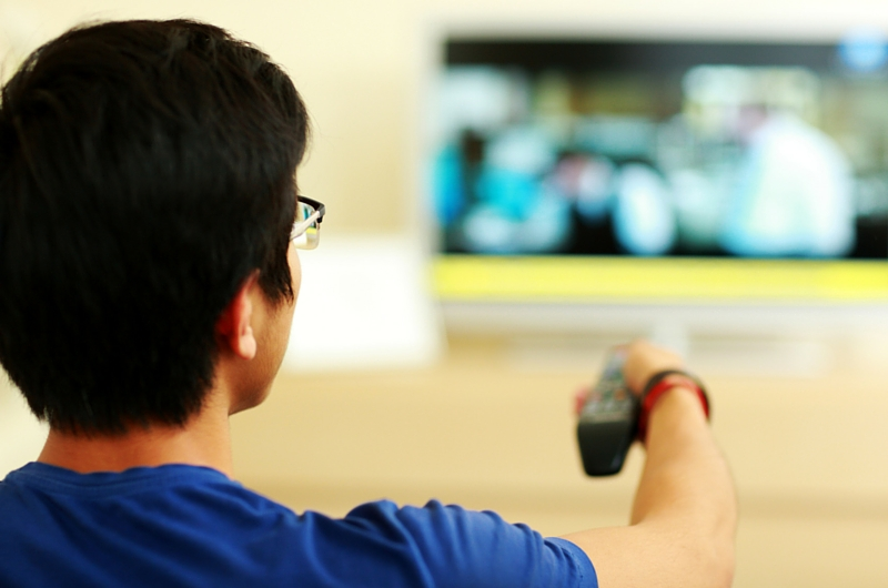 Student changing TV channel with Remote