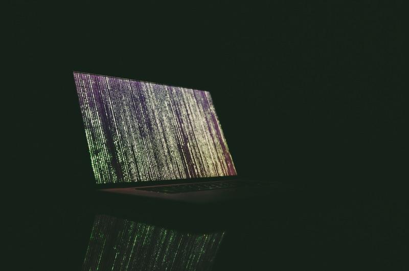 Mac in the dark with binary on screen