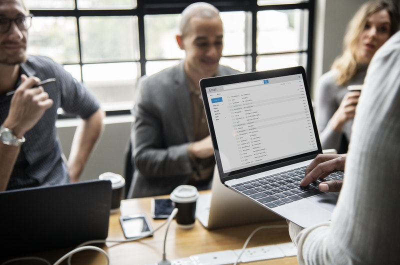 Meeting with person standing checking email on laptop
