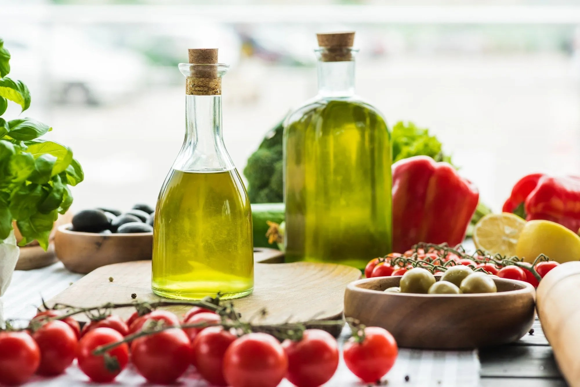olive oil bottles with vegetables on wooden table