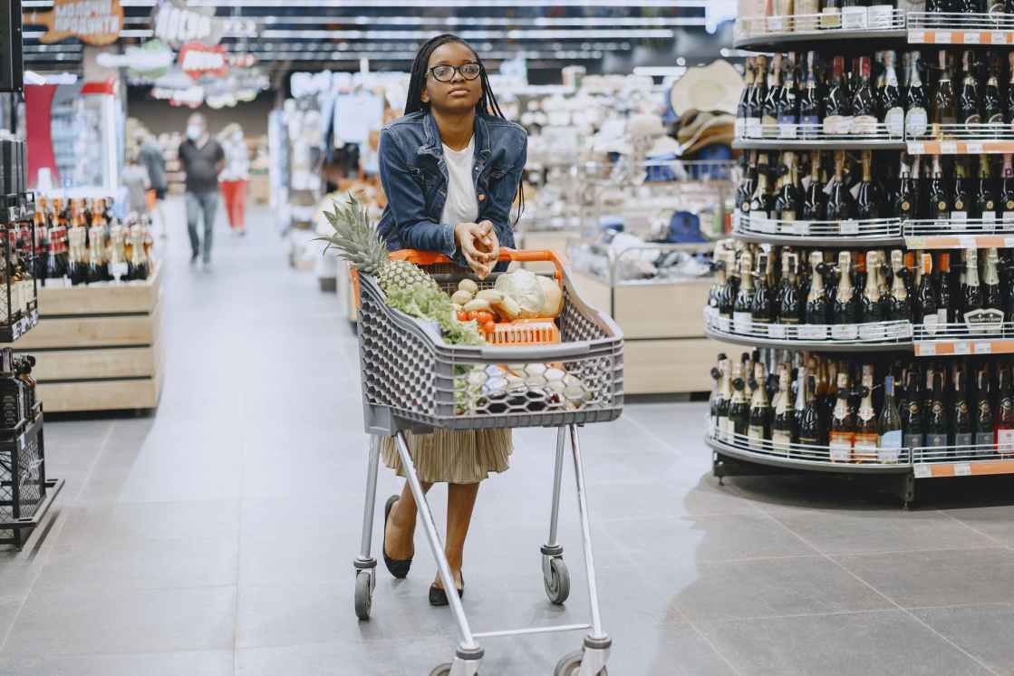 woman in gray jacket and blue denim jeans holding shopping cart