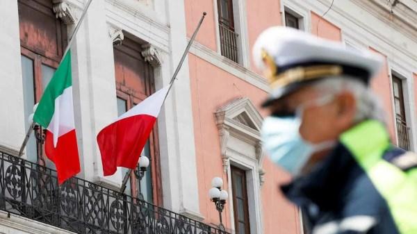 Policial com máscara ao fundo bandeira da itália