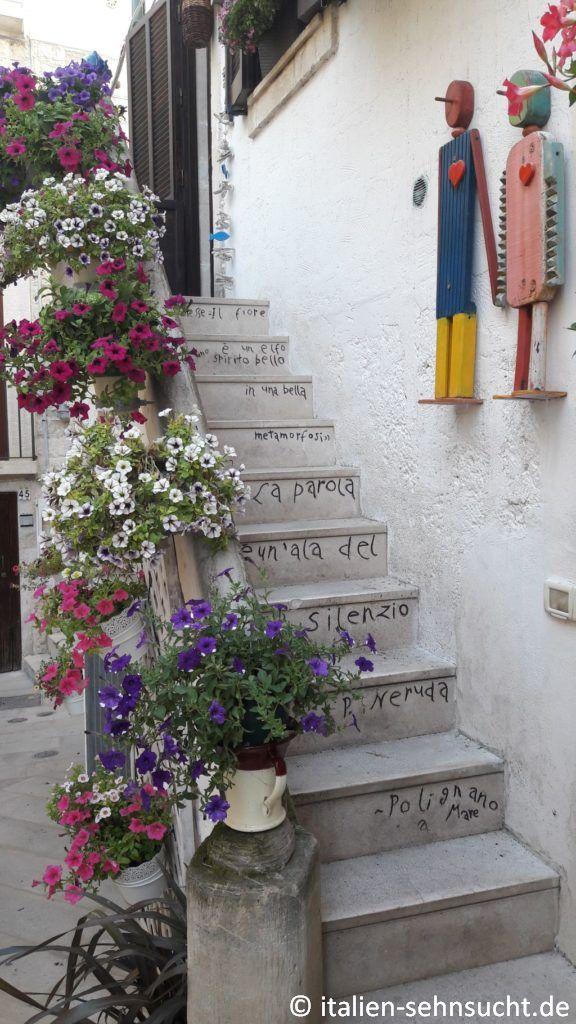 Eine weitere Treppe mit der unvergleichlichen Schrift, üppig geschmückt mit großen, bunten Blumentöpfen.