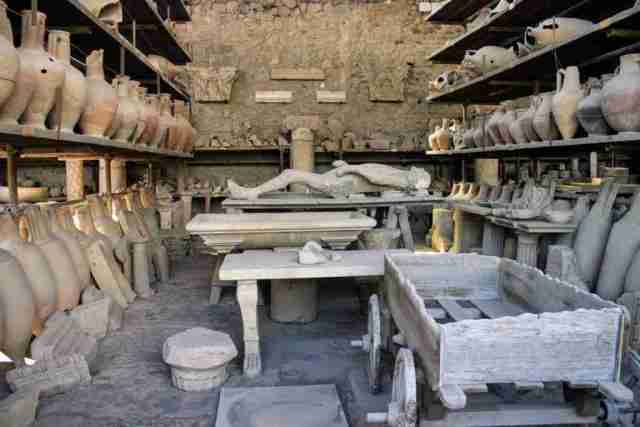 A preserved body lies on a slab in a warehouse of relics found in the ruins of Pompeii