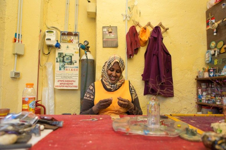Roawda, è scappata dalla guerra in Somalia circa 7 anni fa. Arrivata in Libia, dopo 2 giorni di traversata in mare ha raggiunto prima Lampedusa e poi è stata trasferita a Foggia per 6 mesi. Ora lavora a tempo pieno nel laboratorio di vetro dell'associazione Città Futura.