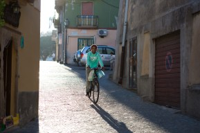 Un ragazzo eritreo porta la spesa in bici per le strade di Riace.