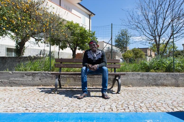 Lamin, 19 anni, è partito dal Gambia per arrivare in Libia e poi in Sicilia. Da 3 mesi è ospite con la sua compagnia in una delle case messe a disposizione dall'amministrazione di Domenico Lucano.