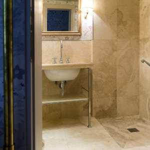 bagno elegante con lavabo e pareti in travertino