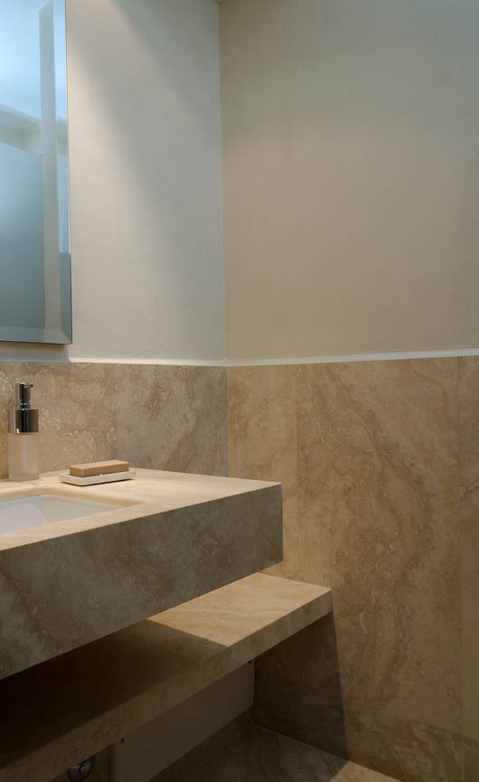 rivestimento in marmo con mobile bagno in travertino