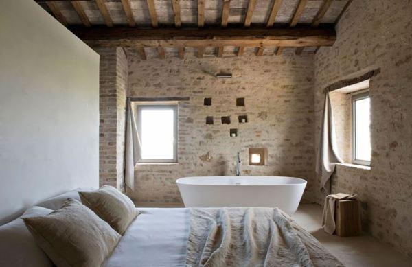 camera con mura in pietra stile rustico bagno e vasca in camera