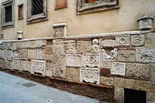 Palazzo Bucelli, col suo basamento di epigrafi ed iscrizioni etrusche e romane in via di Gracciano nel Corso a Montepulciano