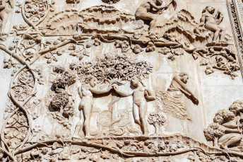Un dettaglio del morso alla mela di Adamo ed Eva, episodio biblico raffigurato sulla facciata del Duomo di Orvieto con una cornice di tralci di vite