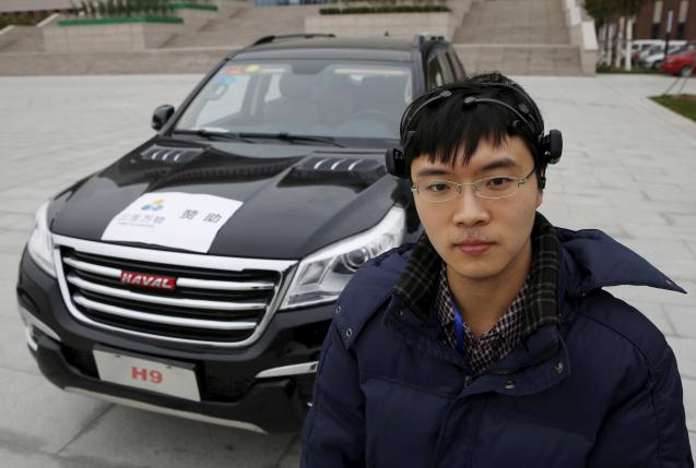 Researcher Zhang Zhao wearing a brain signal-reading equipment poses with a vehicle which can be controlled with his brain wave, during a demonstration at Nankai University in Tianjin