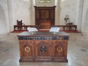 The central Communion table in Christ Church. The Hebrew words across the top say 'do this in remembrance'/ The central design is of a crown over the word Immanuel in Hebrew.