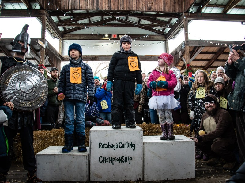 Three children stand on a winners' platform inside the Ithaca Farmers Market at the Rutabaga Curl.