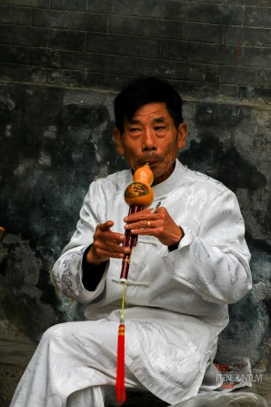 street performer playing a flute in Beijing