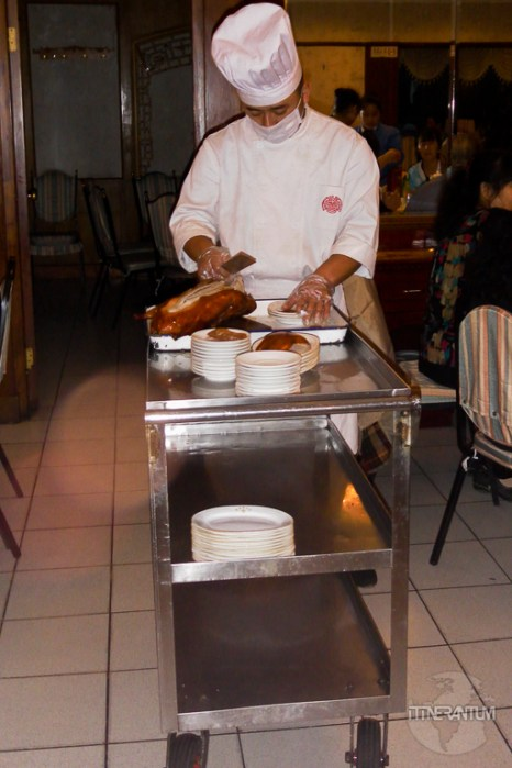 a chef carving a peking duck next to the client's table