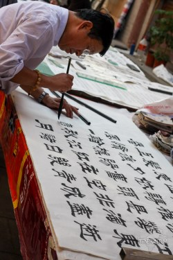 man writing Chinese characters with a brush