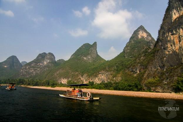 Motor boat on Li River, karst formation on the background