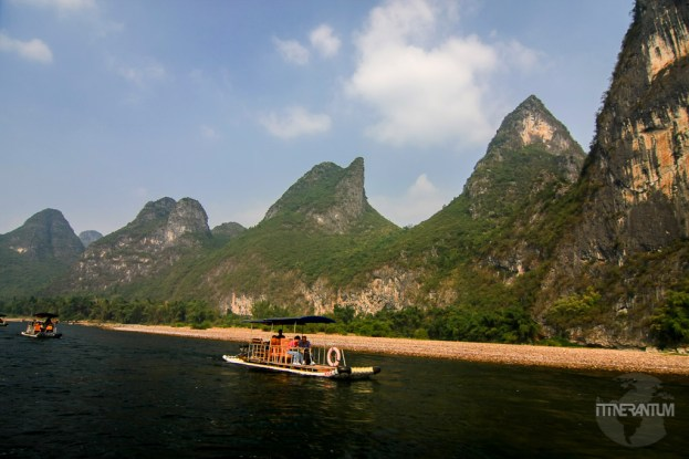Motor boat on Li River, karst formation on the background