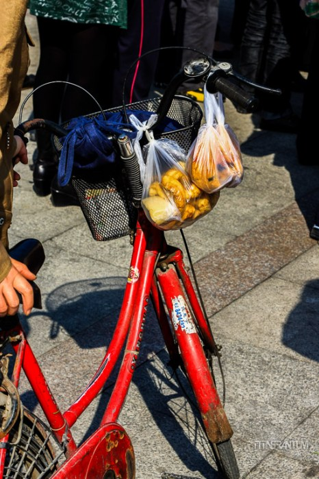 two plastic bags with take away food hanging on a bycicle