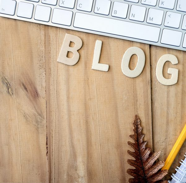 Blogging, blog concepts ideas with white keyboard, noterbook, pencil and wooden letters on wooden background.