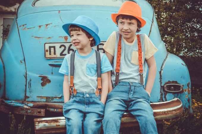 two boys sitting on classic blue car s rear bumper