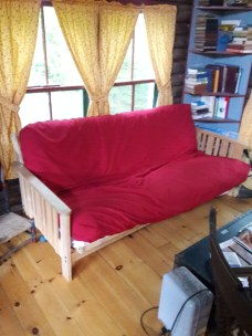 """from the bed looking at the futon in the """"bedroom"""", which is just that end of the cabin"""