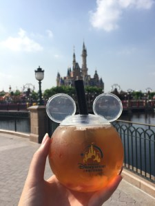 round mickey ears with peach tea and gummies imposed in front of shanghai disney castle