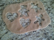Photo of brown felt sheet with cookie cutter shapes cut out