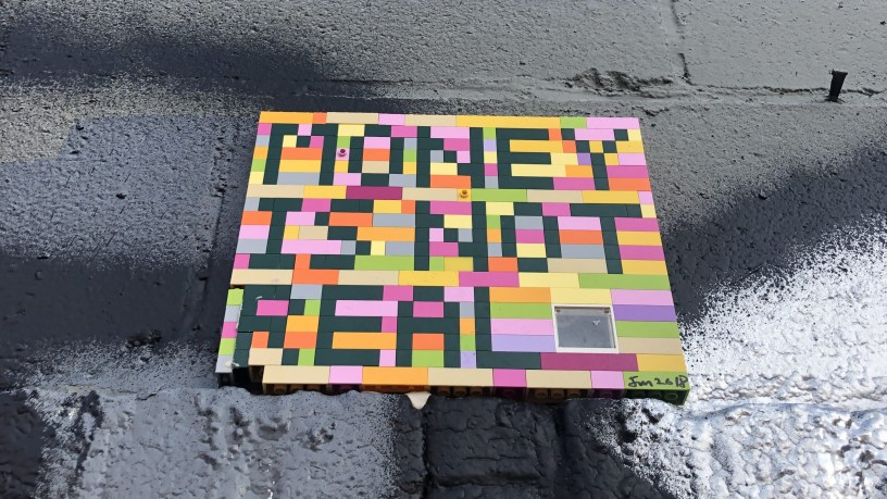 "Piece made out of legos reading ""MONEY IS NOT REAL"""