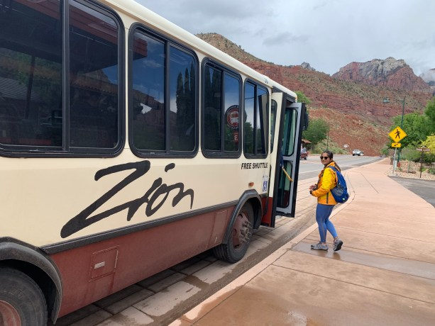 Zion national park shuttle bus with red sandstone cliff in background
