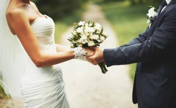 A couple holding bunch of white flowers in wedding