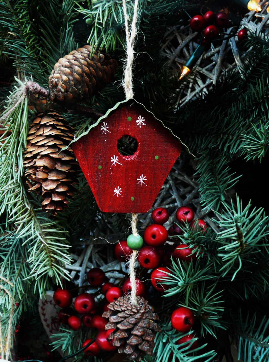 Ornaments on Christmas tree including red berries, red birdhouse and pine cones