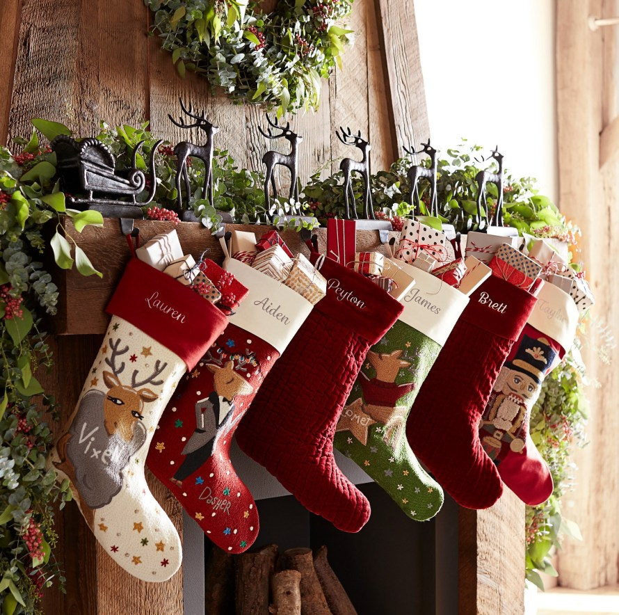 Personalized Christmas Stockings featuring reindeer, nutcracker & one-color themes, hanging from reindeer holders 'pulling' a sleigh