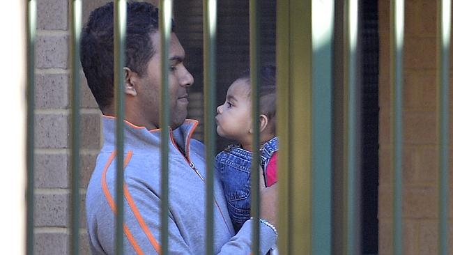 The Sri Lankan father behind detention centre bars with his baby. Picture: Alf Sorbello